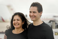 Michael Kovrig embraces his wife Vina Nadjibulla, left, after arriving at Pearson International Airport in Toronto, Saturday, Sept. 25, 2021. China, the U.S. and Canada completed a high-stakes prisoner swap Saturday with joyous homecomings for Kovrig and Michael Spavor, two Canadians held by China and for an executive of Chinese global communications giant Huawei Technologies charged with fraud. (Frank Gunn/The Canadian Press via AP)