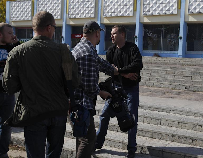 Belarus plainclothes security officer, right, holds a camera, he took away from a journalist, during in Minsk , Tuesday, Sept. 18, 2012. Associated Press photographer Sergei Grtts was beaten and briefly detained by plainclothes security officers in the Belarusian capital. Sergei Grits says he was among eight journalists covering a protest by four opposition activists calling for a boycott of this weekend's parliamentary elections when plainclothes security officers attacked them in downtown Minsk.(AP Photo/Sergei Grits)