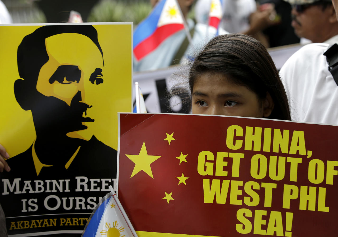 Protesters display placards outside the Chinese Consulate at the financial district of Makati city east of Manila Thursday, June 12, 2014, during a rally against recent reclamation and construction at Mabini Reef in the disputed Spratlys group of islands in the South China Sea. The protesters, who are allied with Philippine President Benigno Aquino III, marked the country's Independence Day Thursday, with a protest rally against China's aggressive moves to reclaim land in the South China Sea where the two countries are locked in an escalating territorial dispute. Figure in placard at left is Apolinario Mabini, a national hero. (AP Photo/Bullit Marquez)