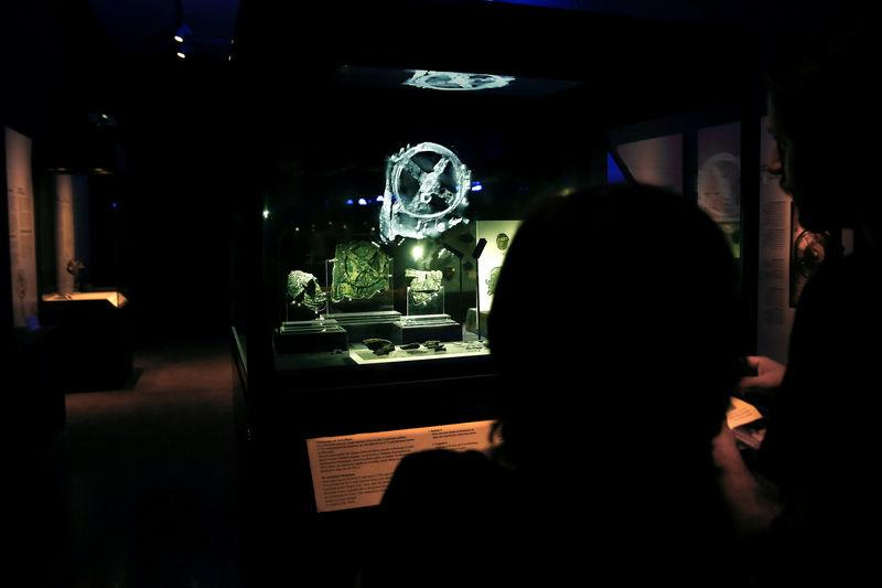 Visitors look at the displayed fragments of the ancient Antikythera Mechanism at the National Archaeological Museum in Athens