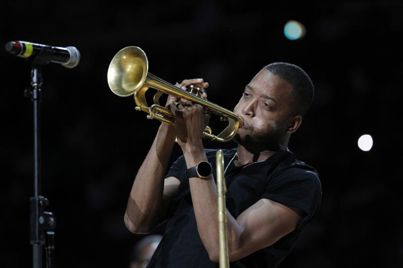 """FILE - This March 14, 2012 file photo shows Troy """"Trombone Shorty"""" Andrews performing at the half time of the New Orleans Hornets Los Angles Lakers NBA basketball game in New Orleans. Andrews and actor Gary Sinise will lead the parade of the Krewe of Orpheus on the evening of Lundi Gras, the day before Fat Tuesday. The celebrity riders were announced Thursday, Dec. 6, 2012, at Mardi Gras World, the huge studio where many Carnival floats are built. Orpheus marks its 20th anniversary when it parades Feb. 11. (AP Photo/Bill Haber)"""