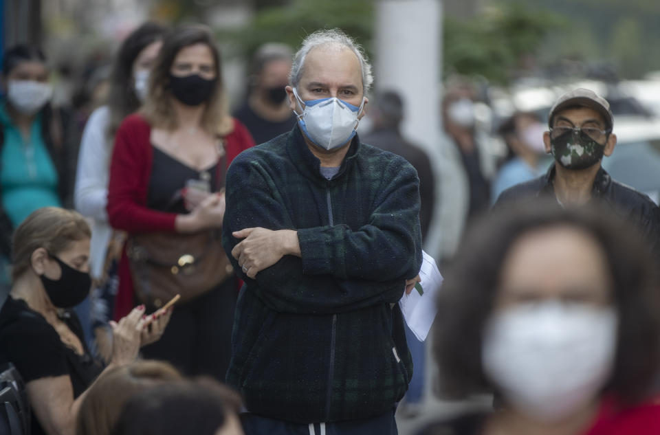 People wait in line outside a community medical center to get a shot of the Pfizer vaccine for COVID-19 in Sao Paulo, Brazil, Thursday, May 6, 2021. (AP Photo/Andre Penner)