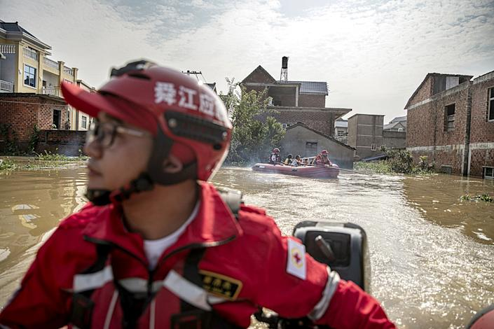 "Rescue volunteers from Ningbo bring villagers back to retrieve items from their flooded homes on July 14. <span class=""copyright"">(Liu Bowen / For The Times)</span>"