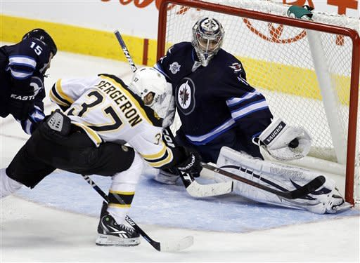 Winnipeg Jets goaltender Ondrej Pavelec (31) makes a save as Boston Bruins' Patrice Bergeron (37) and Jets' Tanner Glass (15) battle in front of the net during the third period of an NHL hockey game, Friday, Feb. 17, 2012, in Winnipeg, Manitoba. The Jets won 4-2. (AP Photo/The Canadian Press, Trevor Hagan)