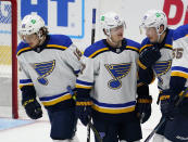 St. Louis Blues center Oskar Sundqvist, right, is congratulated, after scoring a goal, by center Robert Thomas, left, and defenseman Torey Krug during the third period of the team's NHL hockey game against the Colorado Avalanche on Wednesday, Jan. 13, 2021, in Denver. The Blues won 4-1. (AP Photo/David Zalubowski)