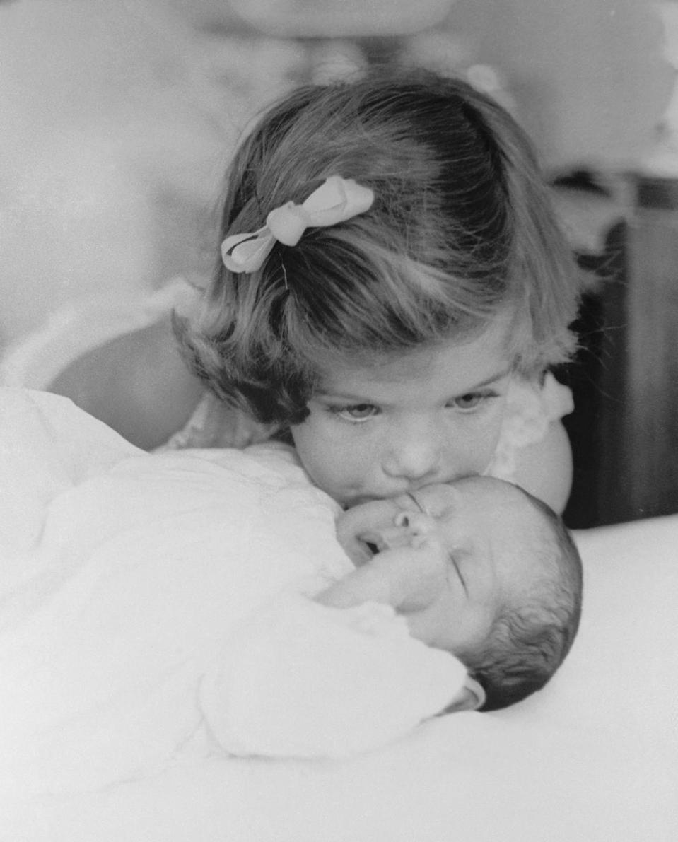 <p>Caroline Kennedy kissing the cheek of her newborn brother John F. Kennedy Jr. </p>