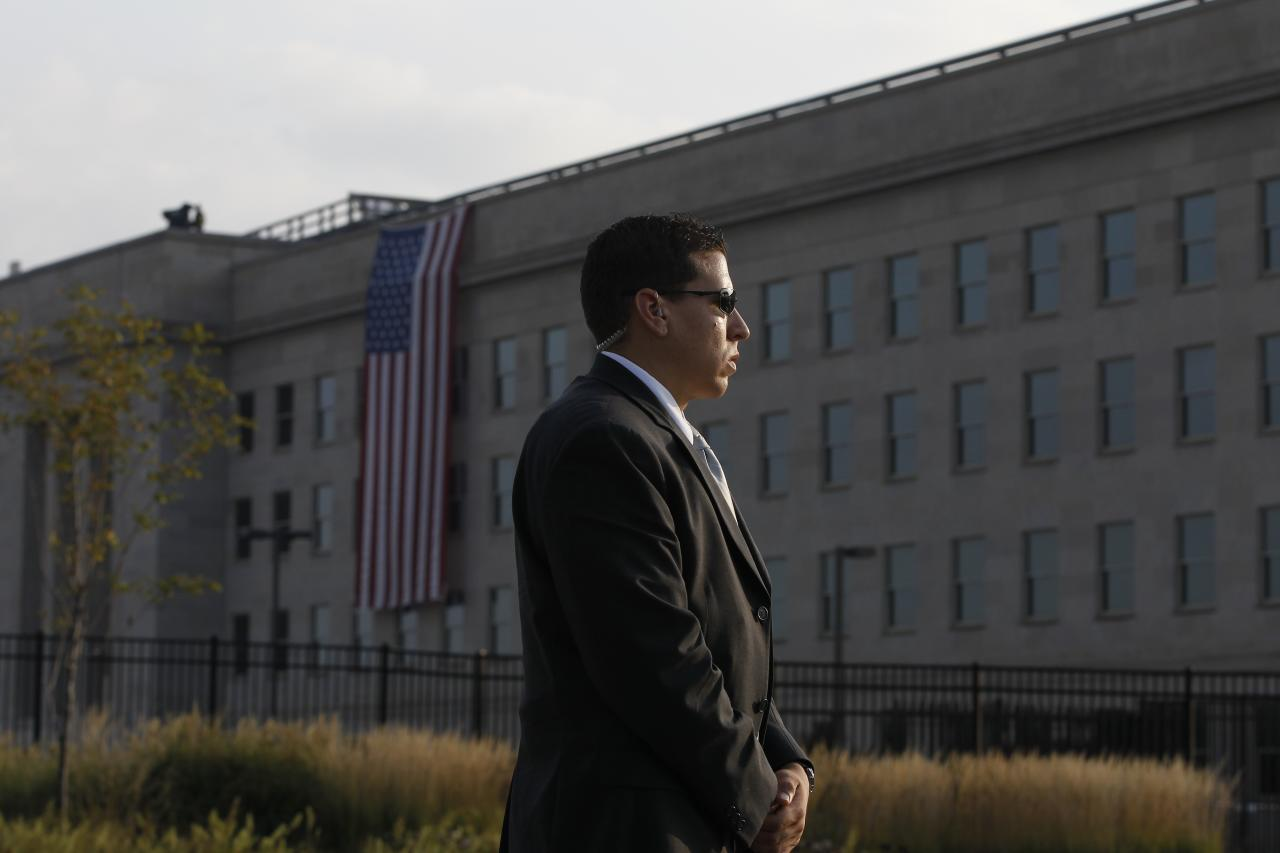A U.S. Secret Service agent stands watch before the start of ceremonies for the 10th anniversary of the September 11 attacks are observed at the Pentagon in Washington, Sunday, Sept. 11, 2011. (AP Photo/Charles Dharapak)