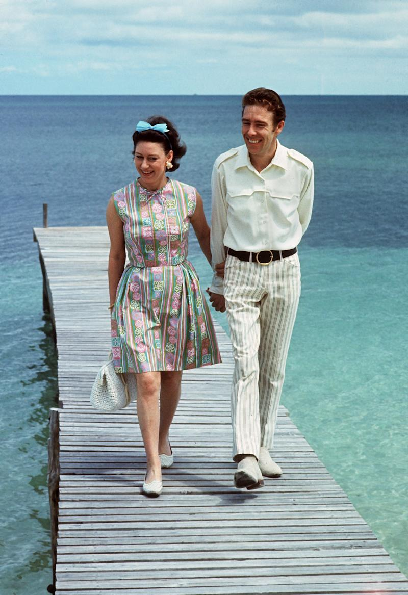 Princess Margaret walks with her husband Earl of Snowdon on a pontoon in the Bahamas. Photo by DALMAS/AFP/Getty Images.