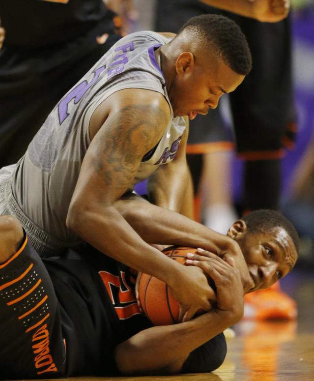 Kansas State guard Marcus Foster (2) and Oklahoma State forward Kamari Murphy (21) go to the floor after a ball during the first half of an NCAA college basketball game in Manhattan, Kan., Saturday, Jan. 4, 2014. (AP Photo/Orlin Wagner)