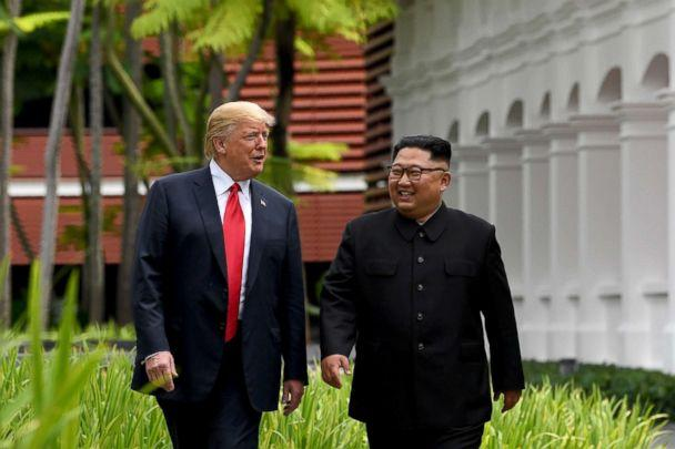 PHOTO: North Korea's leader Kim Jong Un walks with President Donald Trump, left, during a break in talks at their historic US-North Korea summit at the Capella Hotel on Sentosa island in Singapore, June 12, 2018. (Saul Loeb/AFP/Getty Images)