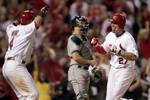 St. Louis Cardinals' Tyler Greene is greeted by teammate Yadier Molina, left, as he crosses home past San Diego Padres catcher Nick Hundley, center, after hitting a two-run home run during the eighth inning of a baseball game Monday, May 21, 2012, in St. Louis. The Cardinals won 4-3. (AP Photo/Jeff Roberson)