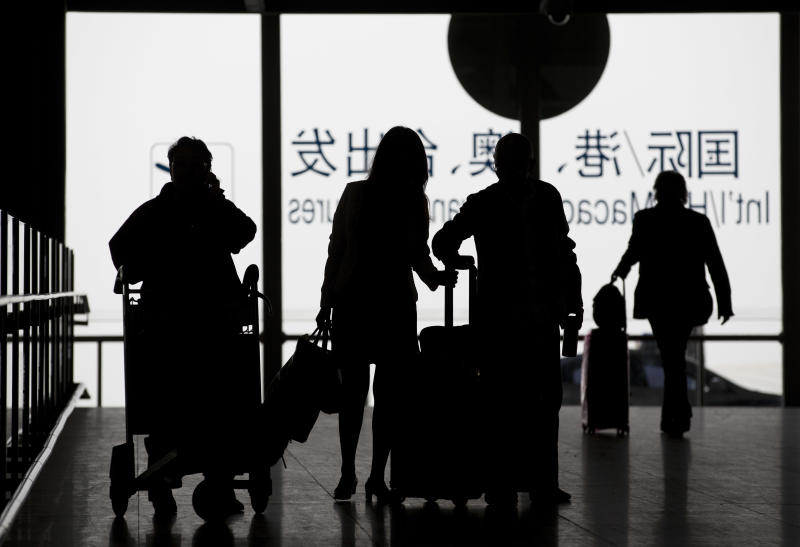 In this April 10, 2014 photo, passengers with their luggage arrive at the Beijing Capital International Airport in Beijing, China. At airports across Asia and around the world, Flight 370 and its 239 passengers and crew, now lost for more than a month, are topics of avid speculation and sometimes anxiety. Passengers typically remain confident about the safety of air travel, but some are distressed by the disappearance, which - given the number of people involved - is unprecedented in aviation industry. (AP Photo/Andy Wong)