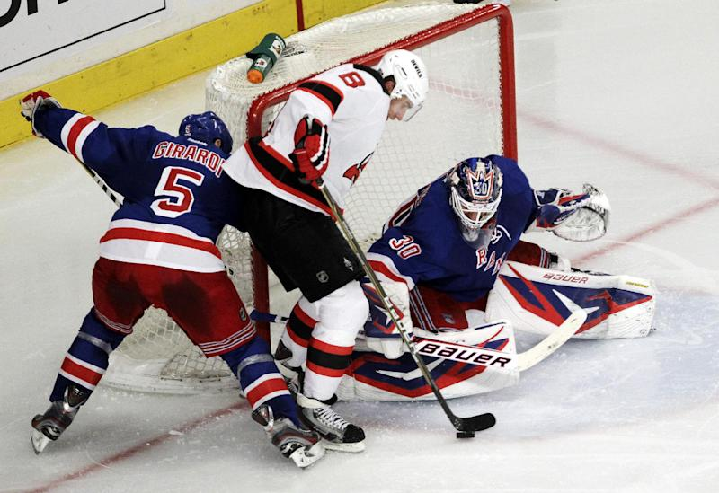 New York Rangers goalie Henrik Lundqvist, right, of Sweden, makes a save as New Jersey Devils' Dainius Zubrus (8), of Lithuania, attacks and Rangers' Dan Girardi (5) defends during the second period of Game 1 of their NHL hockey Stanley Cup Eastern Conference final playoff series, Monday, May 14, 2012, at New York's Madison Square Garden. (AP Photo/Julio Cortez)