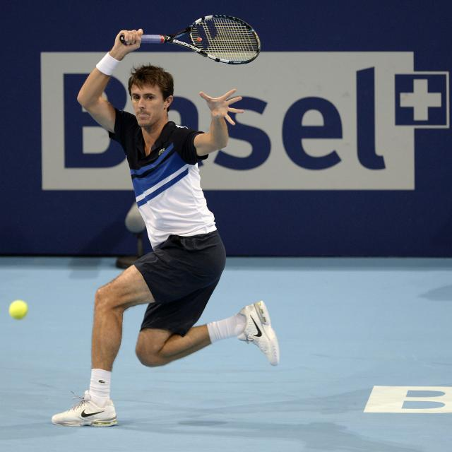 France's Edouard Roger-Vasselin returns a ball to Switzerland's Stanislas Wawrinka during their first round match at the Swiss Indoors tennis tournament at the St. Jakobshalle in Basel, Switzerland, on Tuesday, Oct. 22, 2013. (AP Photo/Keystone,Georgios Kefalas)