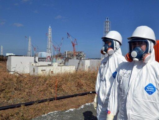 <p>Japanese workers stand near the stricken Fukushima nuclear plant in Okuma. The operator of the crippled Fukushima nuclear plant admitted it had played down the risks of a tsunami to the facility for fear of the financial and regulatory costs.</p>