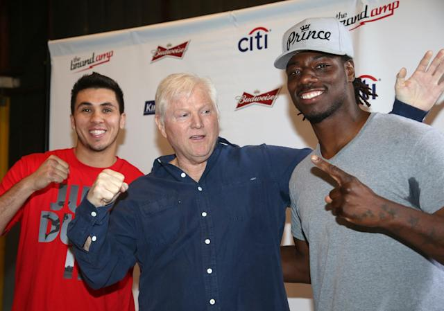 "Michael King, center, president of King Sports, poses with heavyweight boxers Charles Martin, left, and Alex Flores during a weigh-in Tuesday, April 15, 2014, in Santa Monica, Calif., for Wednesday's ""Boxing at Baker"" at the Baker Hangar in Santa Monica, Calif. King is determined to return boxing to its former glory, and the wealthy television executive has spent millions in his pursuit over the last few years. His latest venture is a series of shows in Santa Monica, where he expects Hollywood talent will watch his up-and-coming fighters' growth into stars. (AP Photo/Nick Ut)"