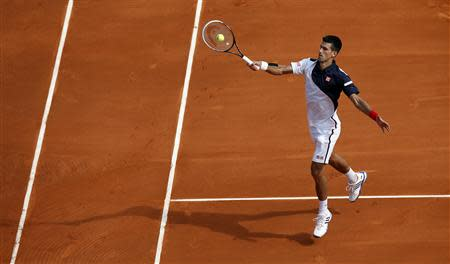 Novak Djokovic of Serbia returns the ball to Albert Montanes of Spain during the Monte Carlo Masters in Monaco April 15, 2014. REUTERS/Eric Gaillard