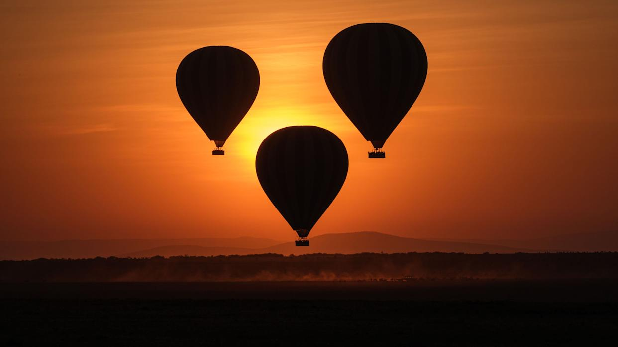 TOPSHOT - Hot-air balloons fly up with tourists at sunrise in the Masai Mara game reserve in Kenya on September 20, 2019. (Photo by Yasuyoshi CHIBA / AFP) (Photo credit should read YASUYOSHI CHIBA/AFP/Getty Images) (Photo: YASUYOSHI CHIBA via Getty Images)