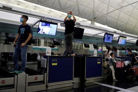Anti-Extradition bill protesters are seen on the check-in counter during a mass demonstration at the Hong Kong international airport, in Hong Kong
