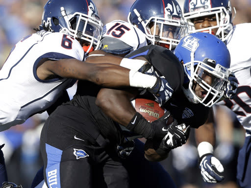 Buffalo running back Branden Oliver, front right, is tackled by Connecticut cornerback Jhavon Williams (6) and safety Ty-Meer Brown (15) during the first half of an NCAA college football game on Saturday, Sept. 28, 2013, in Buffalo, N.Y. (AP Photo/Mike Groll)
