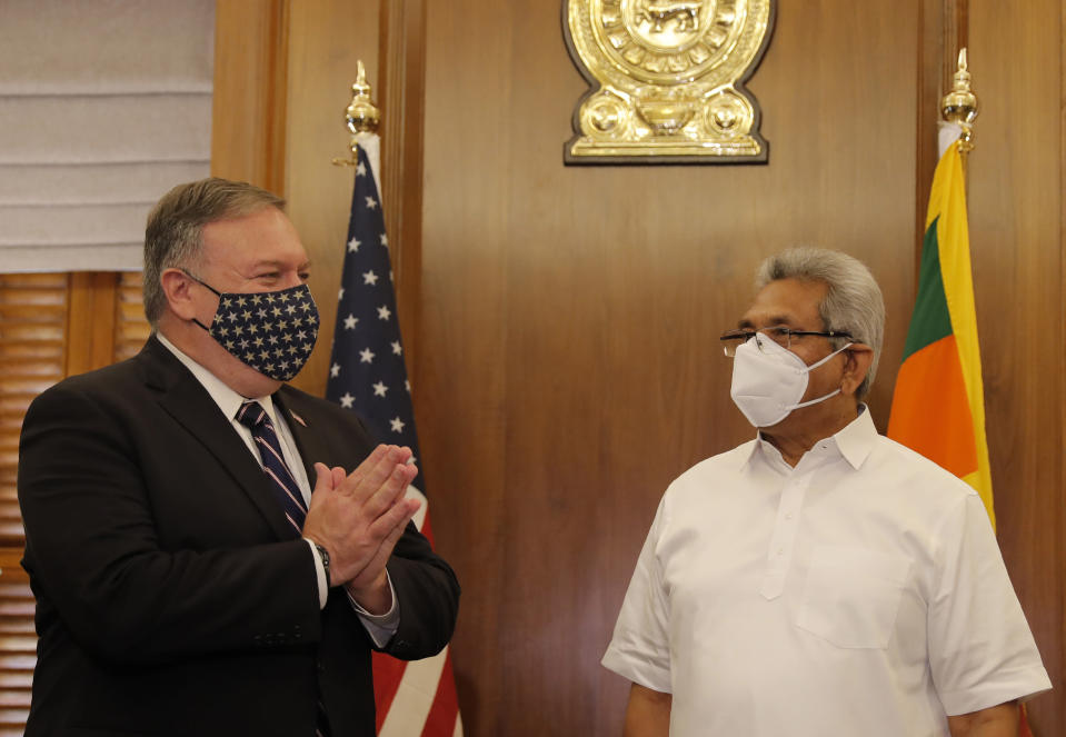 U.S. Secretary of State Mike Pompeo greets Sri Lankan President Gotabaya Rajapksa before their meeting in Colombo, Sri Lanka, Wednesday, Oct. 28, 2020. Pompeo plans to press Sri Lanka to push back against Chinese assertiveness, which U.S. officials complain is highlighted by predatory lending and development projects that benefit China more than the presumed recipients. The Chinese Embassy in Sri Lanka denounced Pompeo's visit to the island even before he arrived there, denouncing a senior U.S. official's warning that the country should be wary of Chinese investment. (AP Photo/Eranga Jayawardena, Pool)