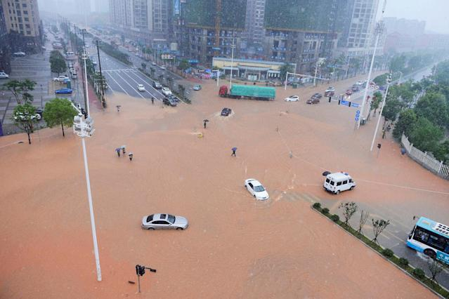 <p>Pedestrians and vehicles cross a flooded street during heavy rain in Changsha, Hunan province, China, July 1, 2017. (Photo: Stringer/Reuters) </p>