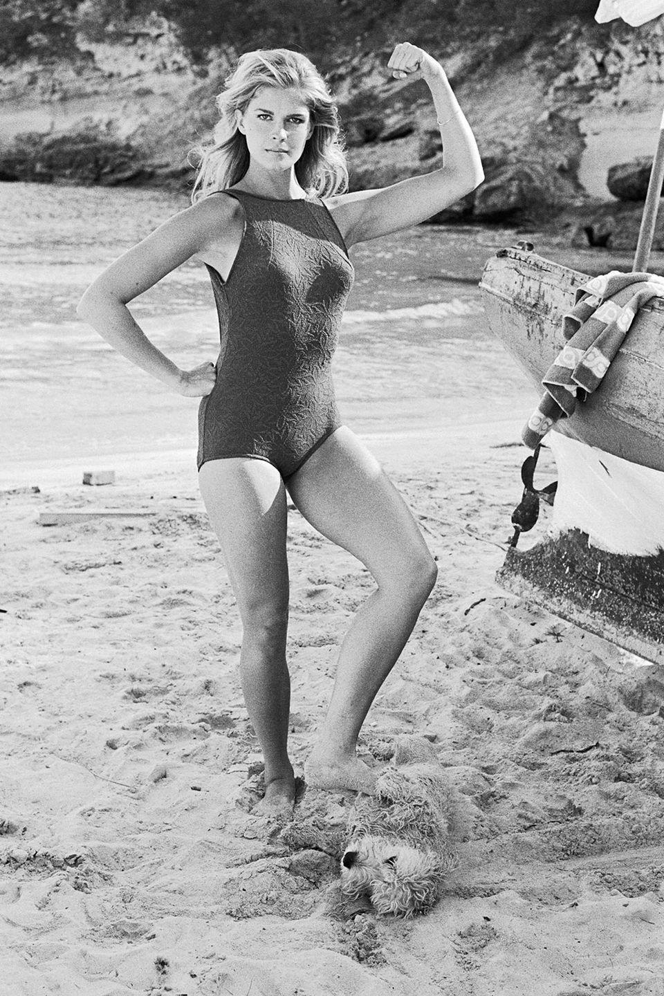 <p>Candice Bergen flexes while resting her foot on a dog laying in the sand in 1968.</p>