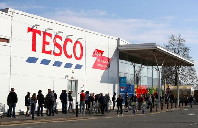 People queue outside a Tesco Extra store in Madeley, Shropshire