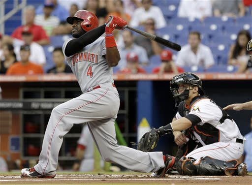Cincinnati Reds' Brandon Phillips (4) follows through on his double against the Miami Marlins in the first inning of a baseball game in Miami, Wednesday, May 15, 2013. Shin-Soo Choo scored on the double. (AP Photo/Alan Diaz)