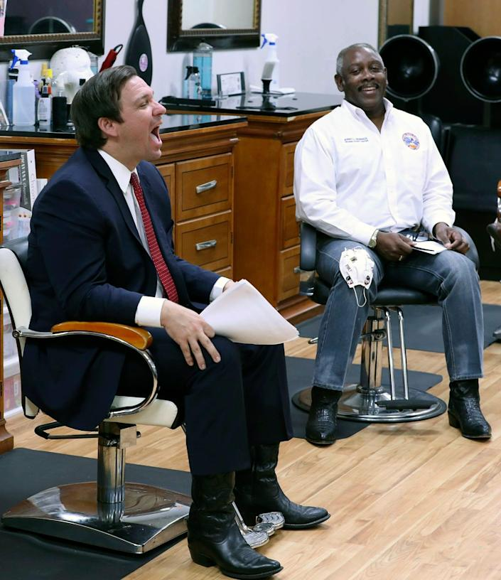 """Florida Gov. Ron DeSantis, left, laughs beside Orange County Mayor Jerry Demings, right, during an appearance at the """"Oh Sooo Jazzy"""" hair salon in Orlando, Fla., Saturday, May 2, 2020. The governor was there to discuss guidelines for reopening businesses during the coronavirus epidemic."""