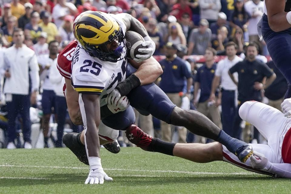 Wisconsin's Danny Vanden Boom stops Michigan's Hassan Haskins during the first half of an NCAA college football game Saturday, Oct. 2, 2021, in Madison, Wis. (AP Photo/Morry Gash)