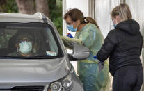 Medical staff test people in their car at a COVID-19 testing station in Wellington, New Zealand, Thursday, June 24, 2021. After enjoying nearly four months without any community transmission of the coronavirus, New Zealanders were on edge Wednesday after health authorities said an infectious traveler from Australia had visited over the weekend. (Mark Mitchell/NZ Herald via AP)