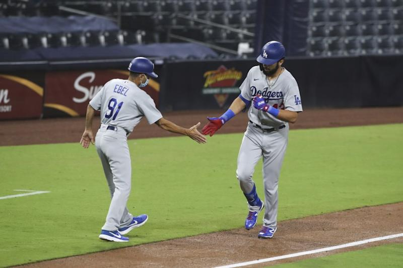 Los Angeles Dodgers third base coach Dino Ebel high fives Edwin Rios as rounds third after hitting a solo home run off San Diego Padres starting pitcher Zach Davies in the fifth inning of a baseball game Tuesday, Sept. 15, 2020, in San Diego. (AP Photo/Derrick Tuskan)