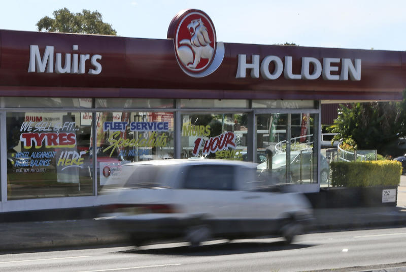 FILE - In this Dec. 11, 2013, file photo, a car drives past a car dealership of Holden, General Motors Co.'s Australian subsidiary, in Sydney, Australia. General Motors decision to pull out of Australia, New Zealand and Thailand as part of a strategy to exit markets that don't produce adequate returns on investments raised dismay Monday, Feb. 17, 2020 from officials concerned over job losses. (AP Photo/Rob Griffith, File)