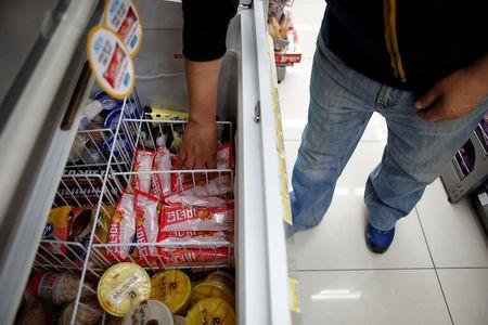 """A clerk arranges ice cream bars named Gyeondyo-bar, which translates to """"hang in there"""" at a convenience store in Seoul, South Korea, May 20, 2016. REUTERS/Kim Hong-Ji"""