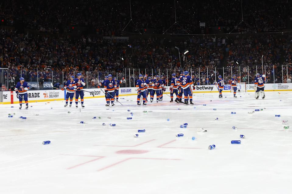 UNIONDALE, NEW YORK - JUNE 23:  The New York Islanders wave to the fans as beer cans are thrown on the ice after their 3-2 overtime victory against the Tampa Bay Lightning in Game Six of the Stanley Cup Semifinals during the 2021 Stanley Cup Playoffs at Nassau Coliseum on June 23, 2021 in Uniondale, New York. (Photo by Bruce Bennett/Getty Images)