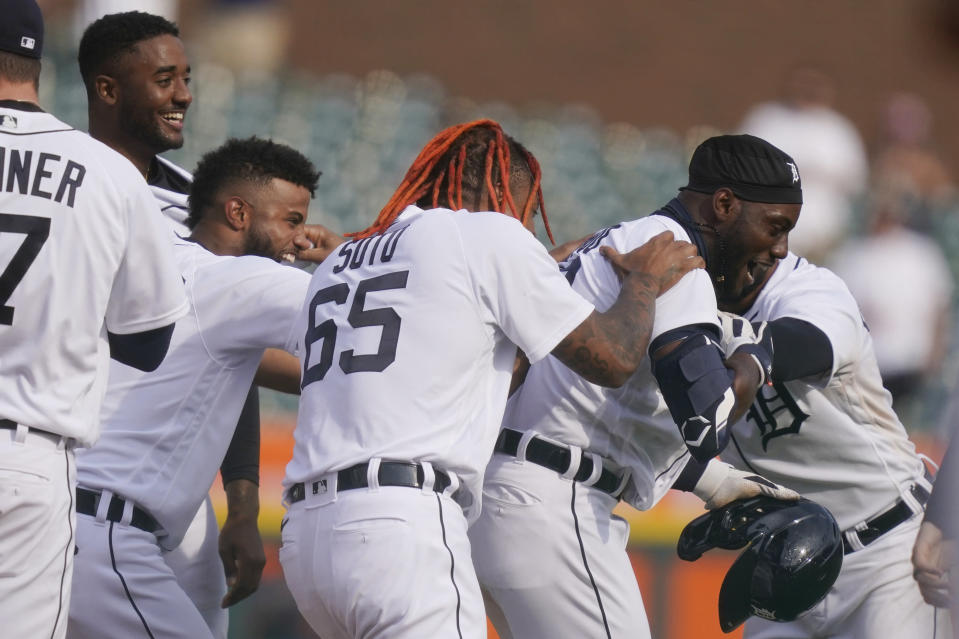 Detroit Tigers' Akil Baddoo, right, is swarmed by teammates after hitting the walk off game winning run during the tenth inning of a baseball game against the Minnesota Twins, Tuesday, April 6, 2021, in Detroit. (AP Photo/Carlos Osorio)