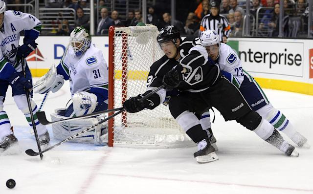 Los Angeles Kings right wing Dustin Brown, center, tries to get a shot in on Vancouver Canucks goalie Eddie Lack, left, of Sweden, as defenseman Alexander Edler, of Sweden, puts pressure on him during the second period of an NHL hockey game, Saturday, Nov. 9, 2013, in Los Angeles. (AP Photo/Mark J. Terrill)