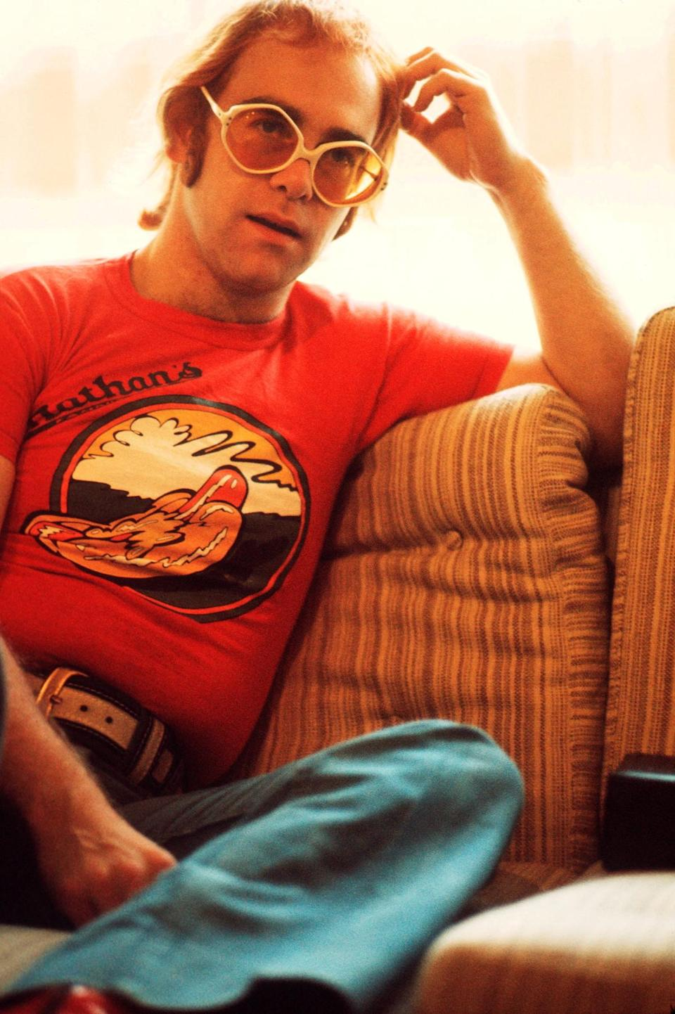 <p>Elton John in a relaxed Nathan's Hot Dog T-shirt and yellow tinted sunglasses in 1974. (Photo: Getty Images) </p>