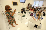 FILE - In this Aug. 6, 2020, file photo Diane Floyd, a seventh grade math teacher at Guntown Middle School, goes over the daily schedule and bell times with her new students on their first day back to school for the Lee County District in Guntown, Miss. As schools reopen around the country, their ability to quickly identify and contain coronavirus outbreaks before they get out of hand is about to be put to the test. (Adam Robison/The Northeast Mississippi Daily Journal via AP, File)