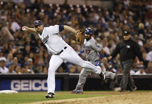 San Diego Padres third baseman Chase Headley prepares tp fire a throw after fielding a slow roller hit by Los Angeles Dodgers' Hanley Ramirez as the Dodgers' Matt Kemp rounds third during sixth inning of a baseball game Tuesday, Sept. 25, 2012 in San Diego. (AP Photo/Lenny Ignelzi)