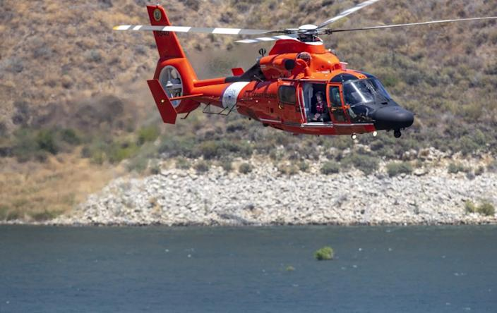 """A Coast Guard helicopter assisting in the search for Naya Rivera flies over Lake Piru on Thursday. <span class=""""copyright"""">(Brian van der Brug / Los Angeles Times)</span>"""