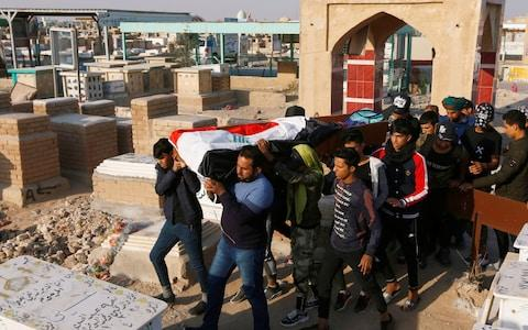 Mourners carry the coffin of a demonstrator who was killed at an anti-government protest, during a funeral at a cemetery in Najaf - Credit: Reuters