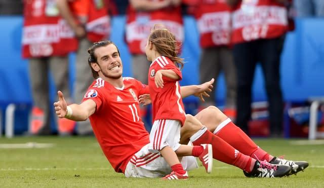 Gareth Bale celebrated with daughter Alba Violet on the pitch after the round of 16 victory against Northern Ireland in Paris (Joe Giddens/PA)
