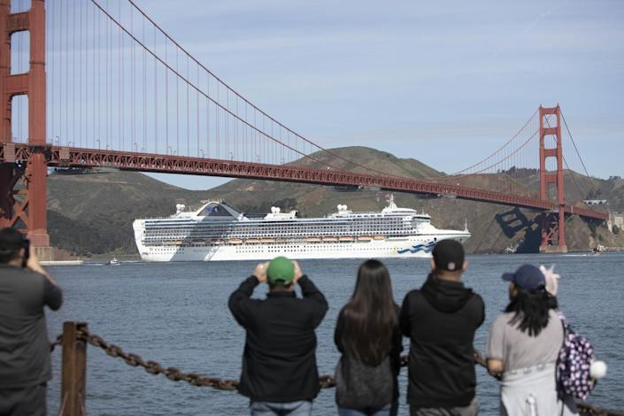 People watch the Grand Princess cruise ship sail under the Golden Gate Bridge in March 2020.