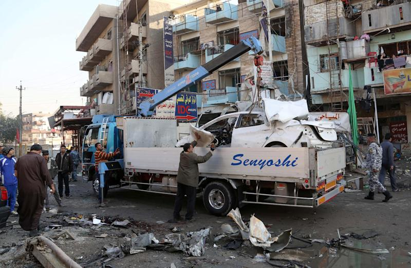Municipality workers remove debris while civilians inspect the site of a car bomb attack at an outdoor market in Baghdad al-Jadidah district, Iraq, Monday, Jan. 20, 2014. A series of bombings in central Iraq killed dozens of people on Monday, as a government official claimed that al-Qaida-linked fighters have dug in to a city they seized last month and possess enough heavy weapons to storm into the country's capital. (AP Photo/Khalid Mohammed)