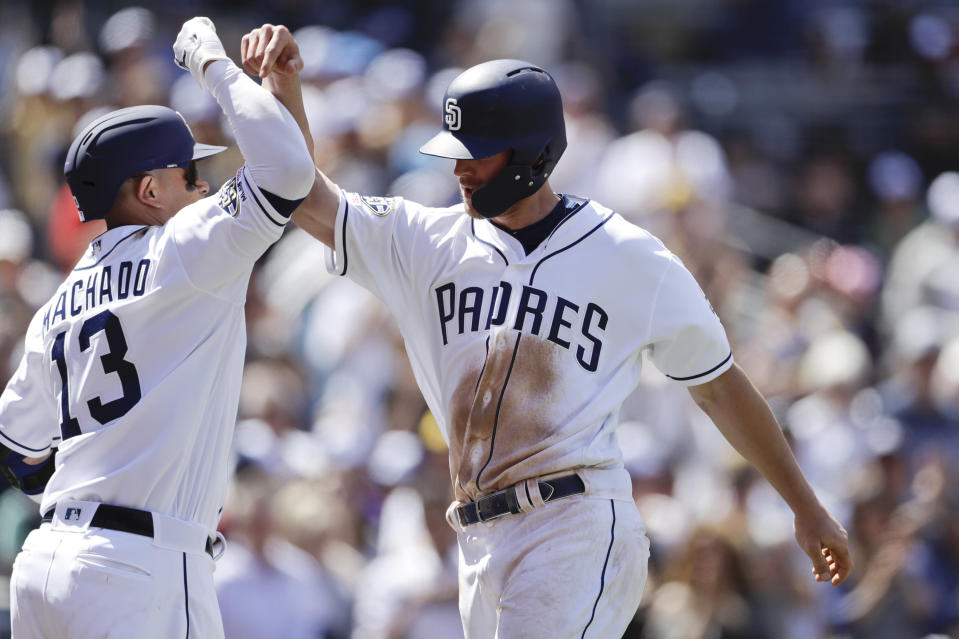 San Diego Padres' Wil Myers, right, is greeted by teammate Manny Machado, left, after hitting a home run during the third inning of a baseball game against the San Francisco Giants, Thursday, March 28, 2019, in San Diego. (AP Photo/Gregory Bull)