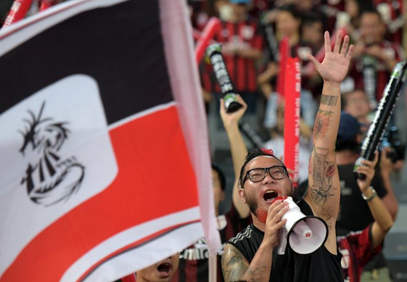 AC Milan supporter Liu Shu cheers for his team ahead of the International Champions Cup football match between AC Milan and  Inter Milan in Shenzhen on July 25, 2015