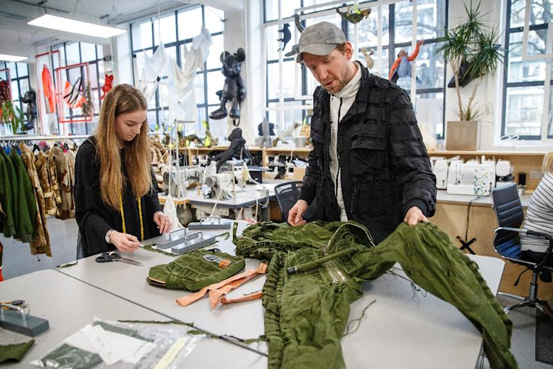 Christopher Raeburn working with a MIG jet fighter jumpsuit that is being turned into hand bags at his studio in Hackney east London