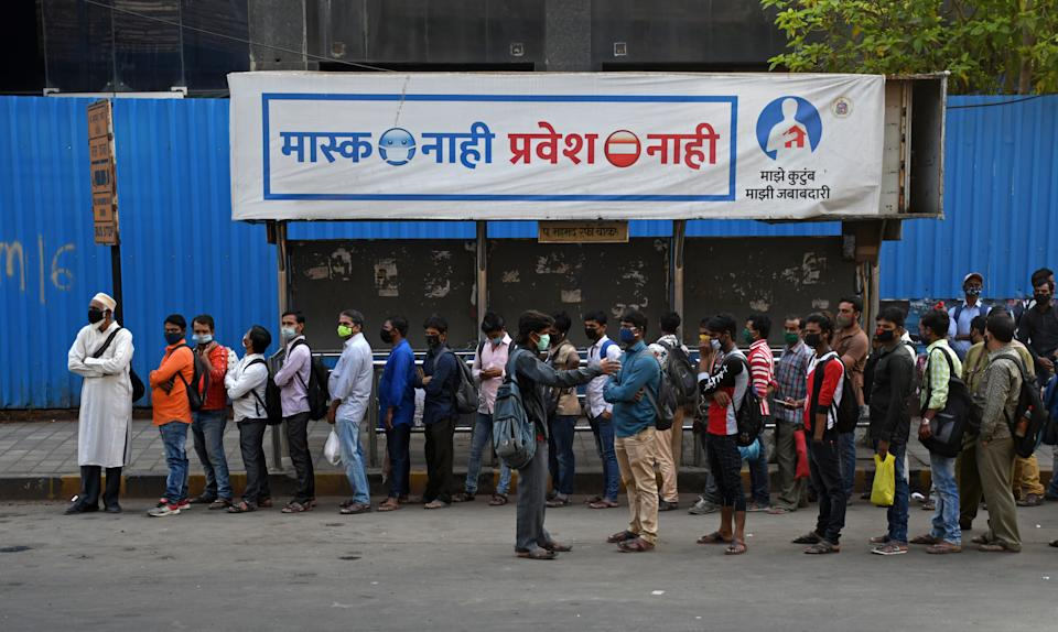 MUMBAI, MAHARASHTRA, INDIA - 2021/02/25: People stand in a queue at a bus shelter in Mumbai. Covid-19 cases are spiraling in Maharashtra state as people are not maintaining social distance while travelling to work. (Photo by Ashish Vaishnav/SOPA Images/LightRocket via Getty Images)